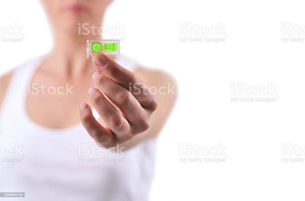 Young woman holding a spirit level on her hand stock photo