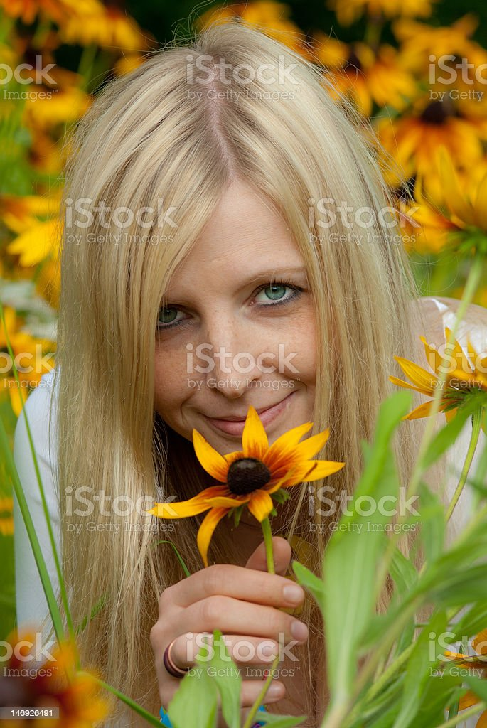 Young woman holding a yellow flower and smiling stock photo