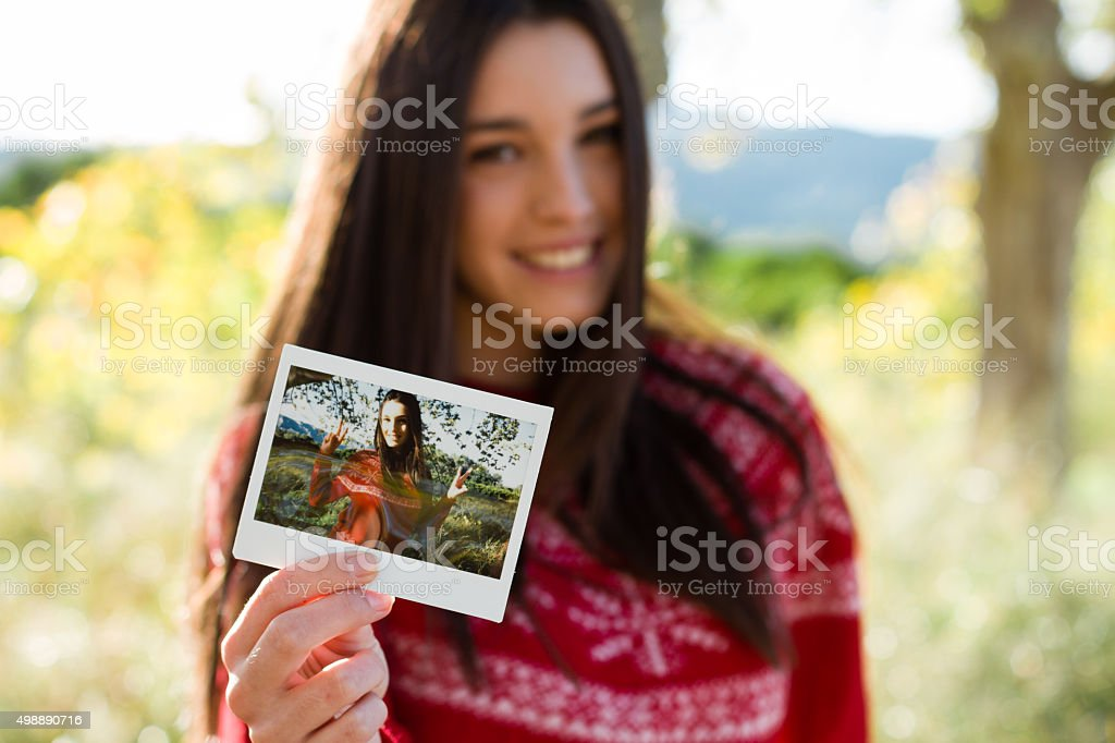 Young woman holding an instant photo stock photo
