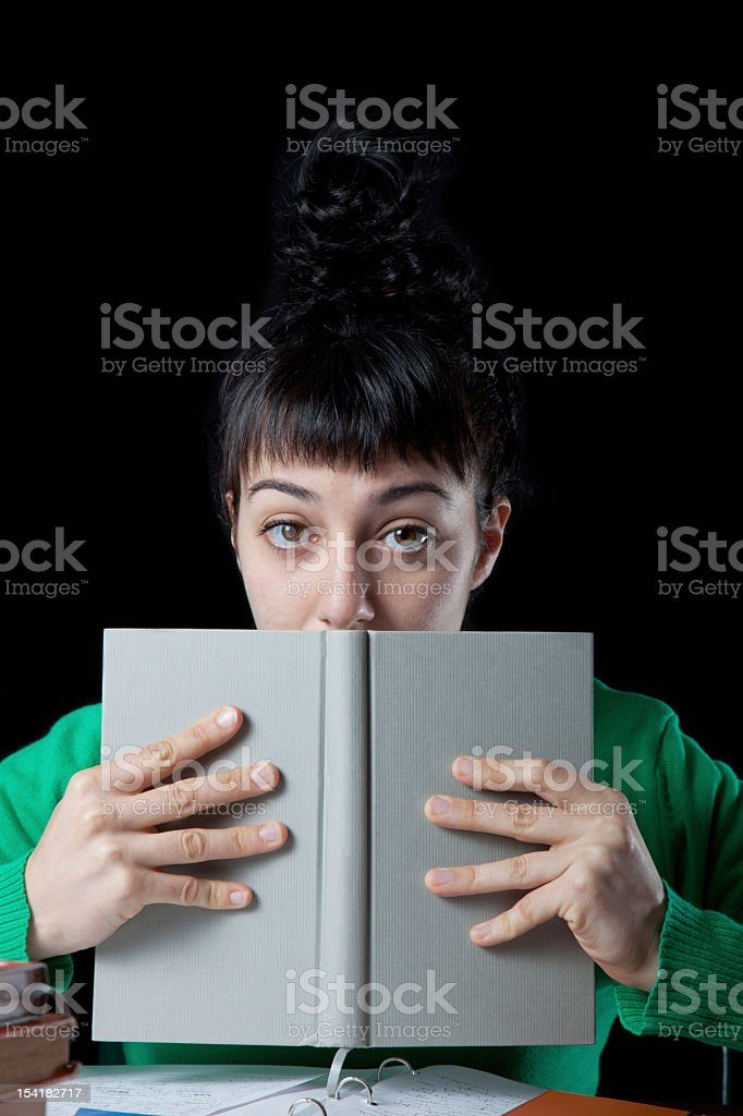 Young woman holding and covering mouth with book royalty-free stock photo