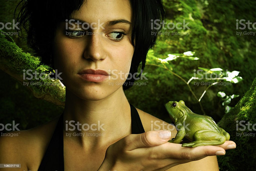 Young Woman Holding and Looking at Frog royalty-free stock photo