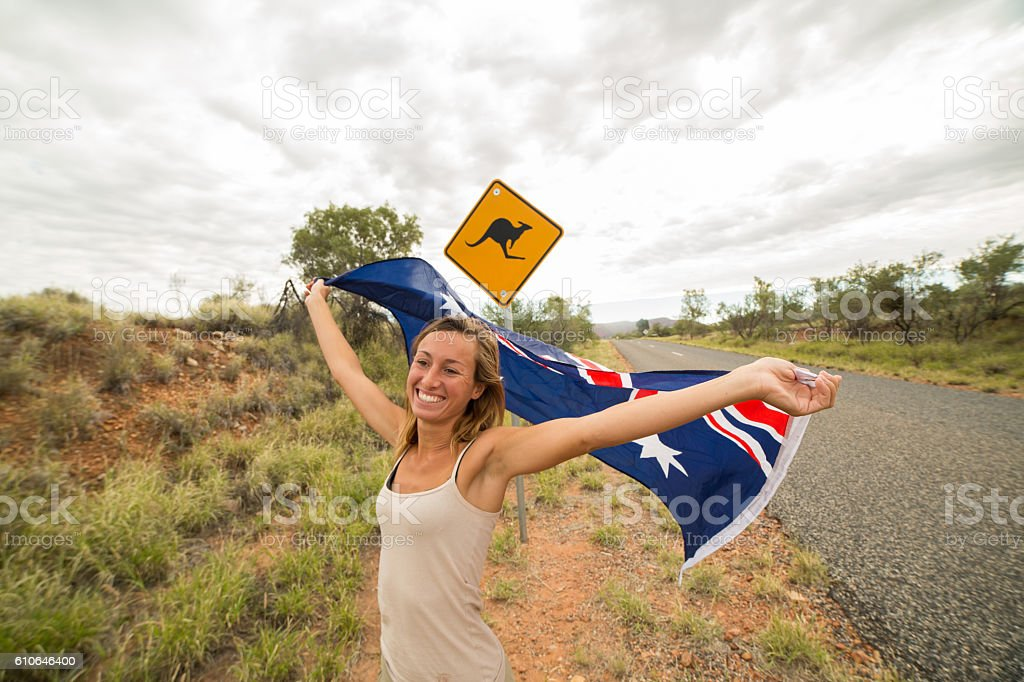 Young woman holding Australian flag in air near Kangaroo sign stock photo