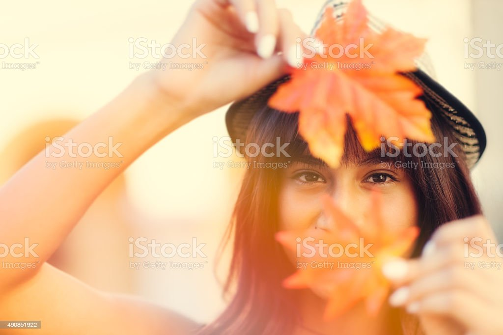 Young woman holding Autumn leafs in hands stock photo