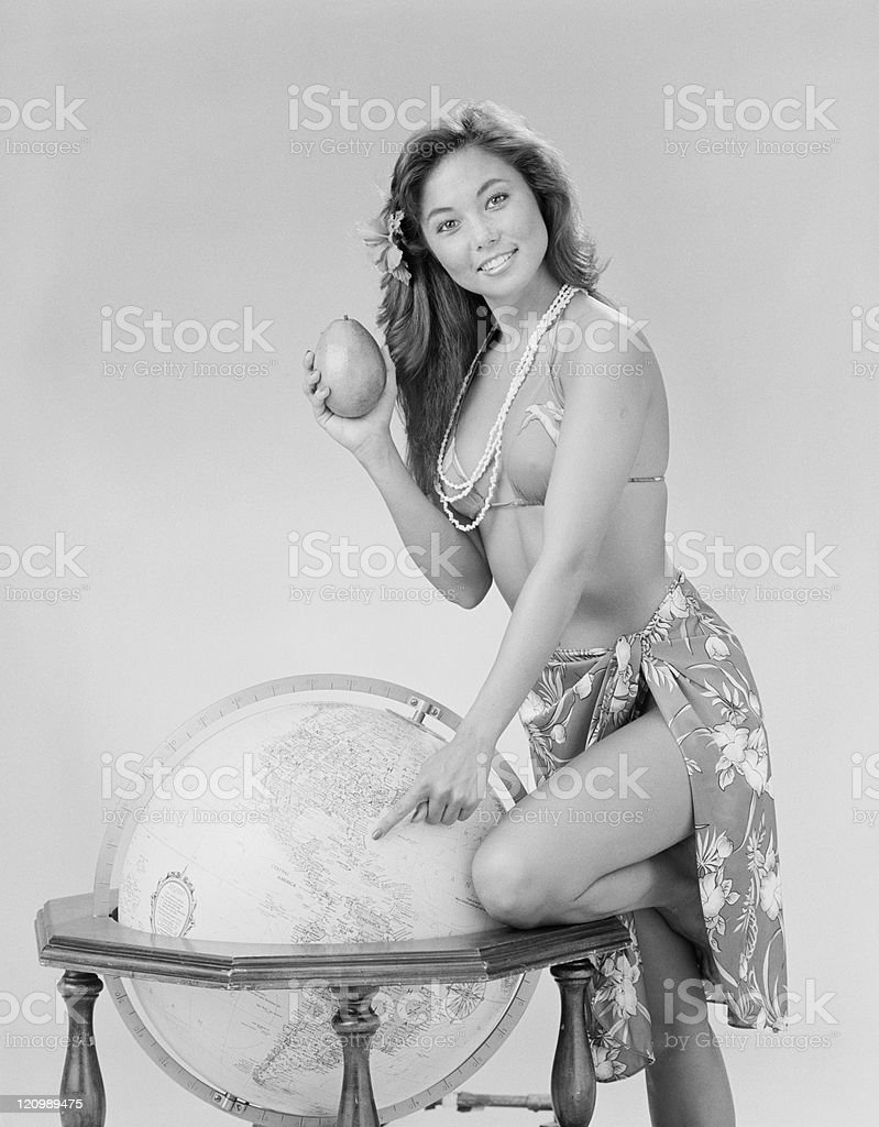 Young woman holding avocado and pointing on globe, smiling, portrait  royalty-free stock photo