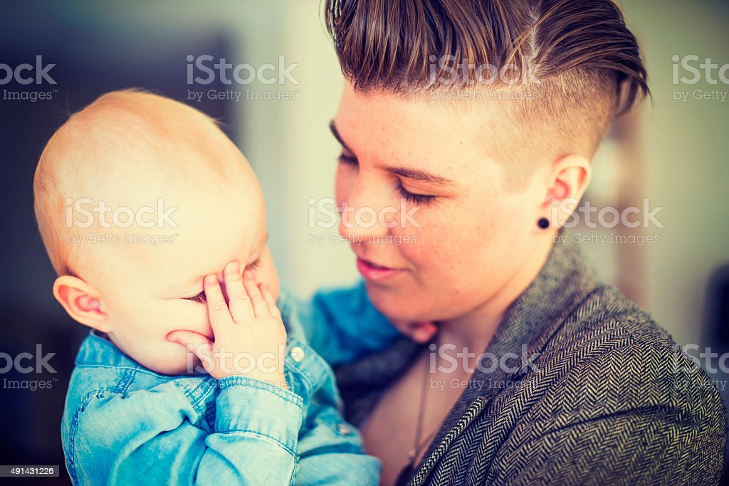 Young woman holding baby with hand on face at home stock photo