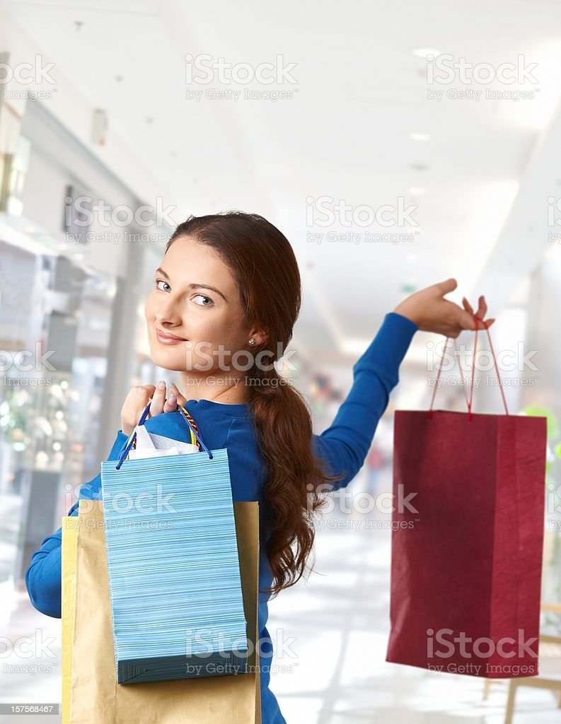 Young woman holding bags in shopping mall royalty-free stock photo