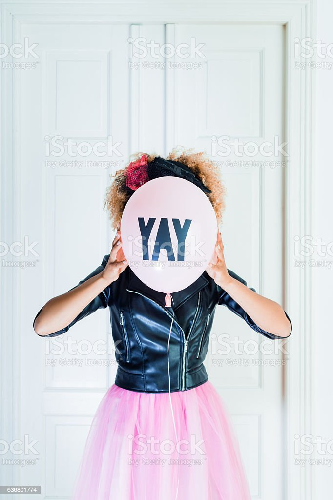 Young woman holding balloon in front of her face stock photo