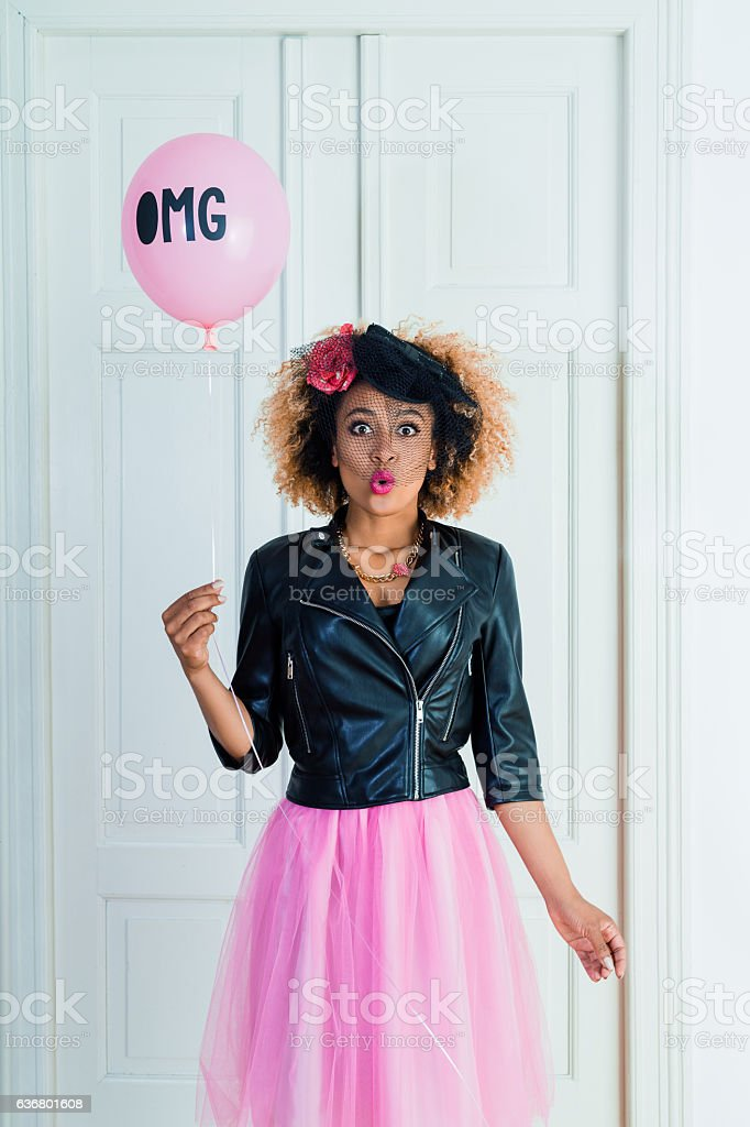Young woman holding balloon with text OMG stock photo