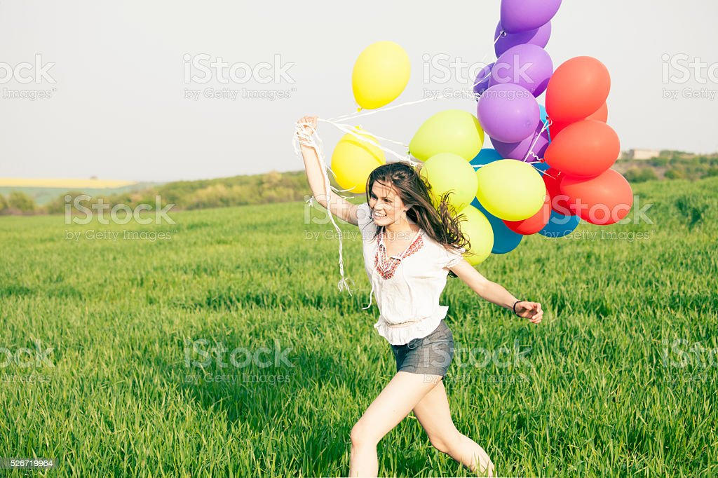 Young woman holding balloons blown away by the wind stock photo