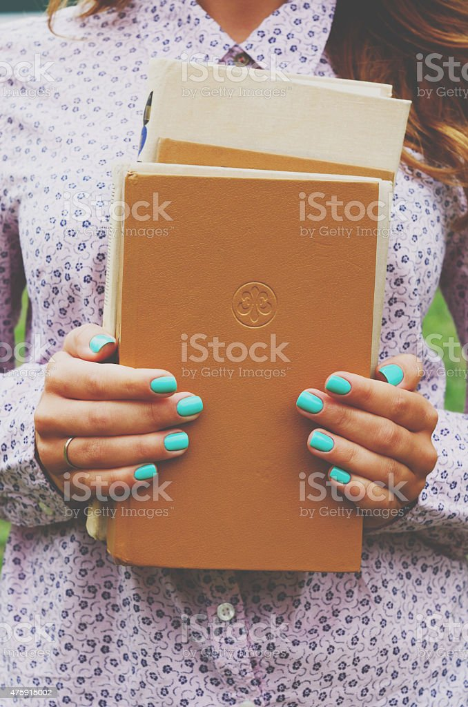 Young woman holding book pile in her hands stock photo