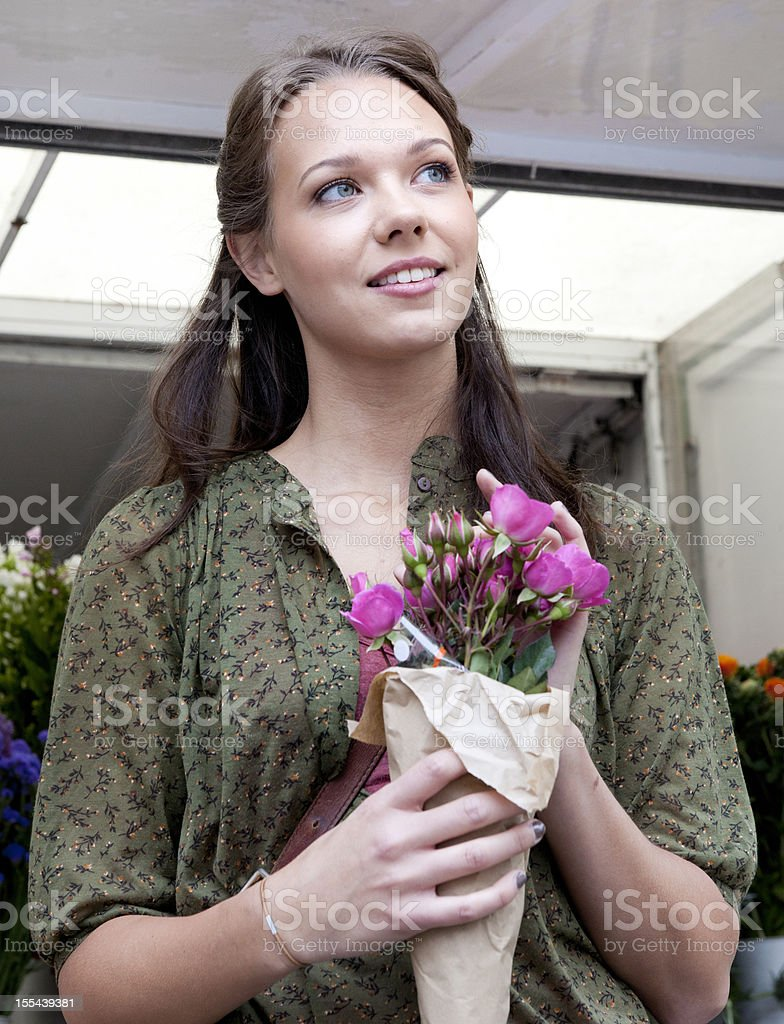 young woman holding bouquet of roses at flower market stall royalty-free stock photo