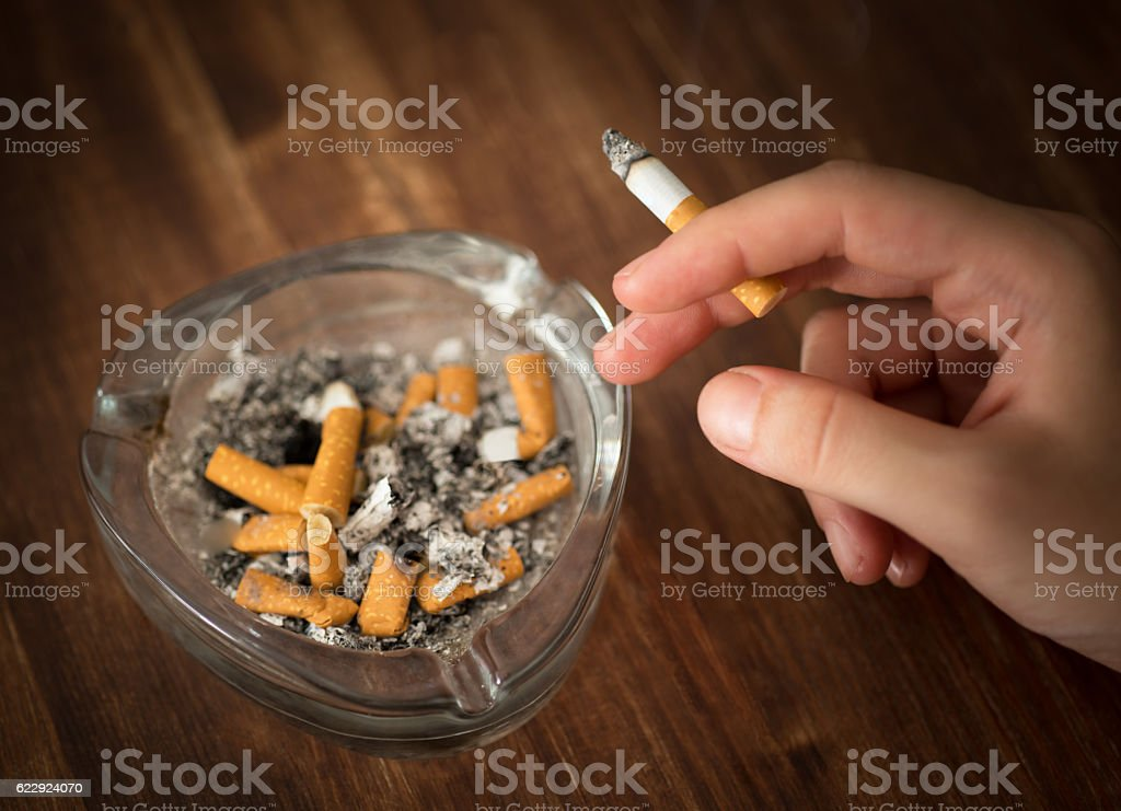 Young woman holding burning cigarette in hand stock photo