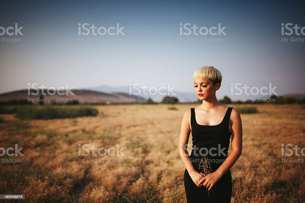 Young woman holding bush on posing on the field stock photo