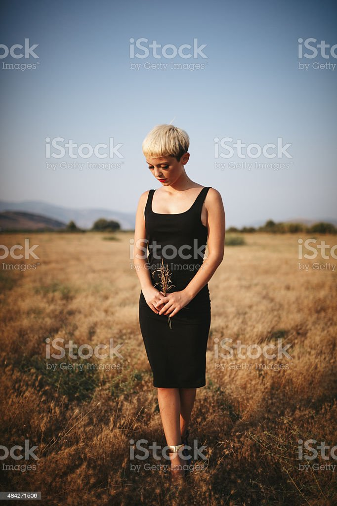 Young woman holding bush on the field stock photo