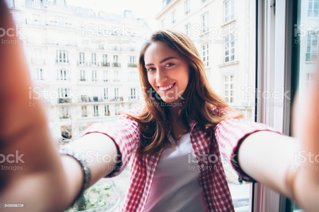 Young woman holding camera and making selfie stock photo