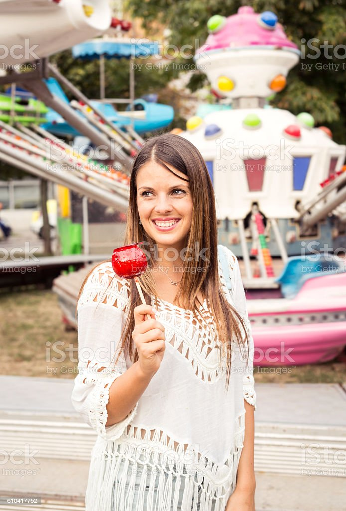 young woman holding candy apple and enjoying outdoor stock photo