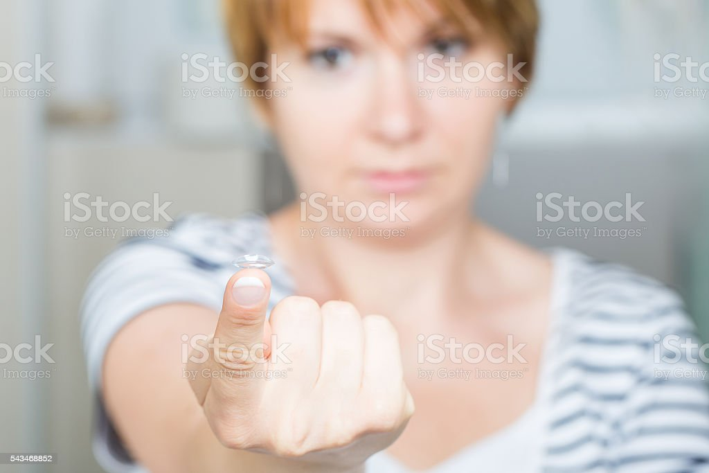 Young woman holding contact lens on finger stock photo