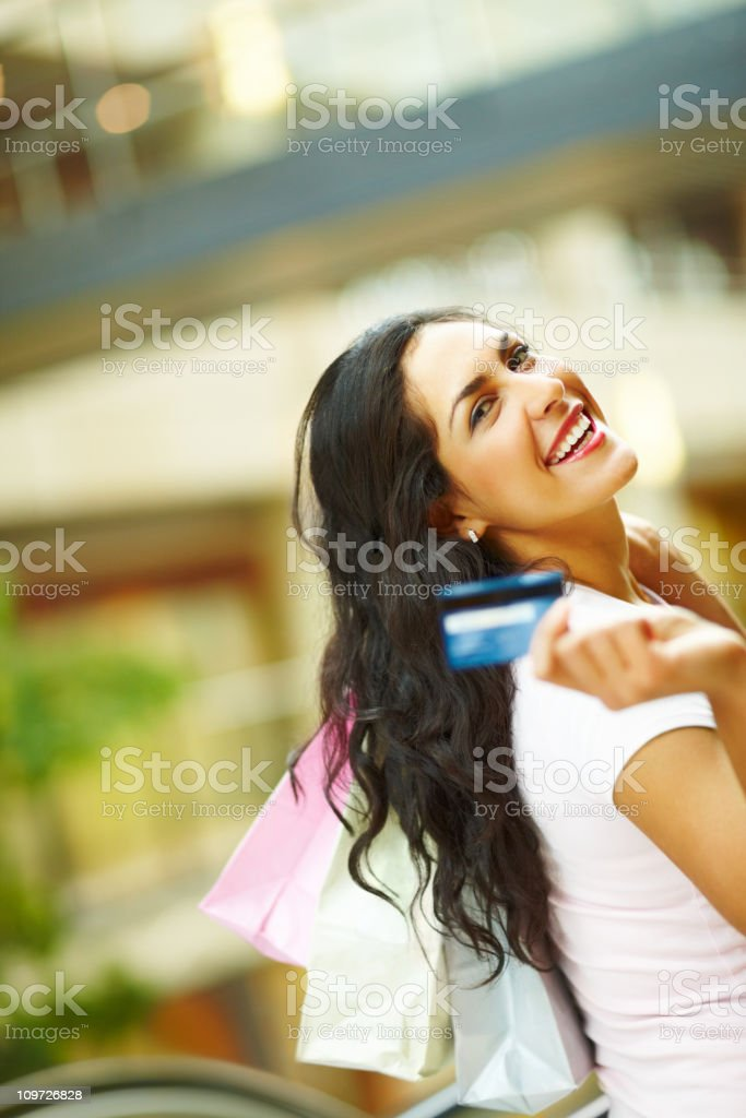 Young woman holding credit card and carrying shopping bags royalty-free stock photo