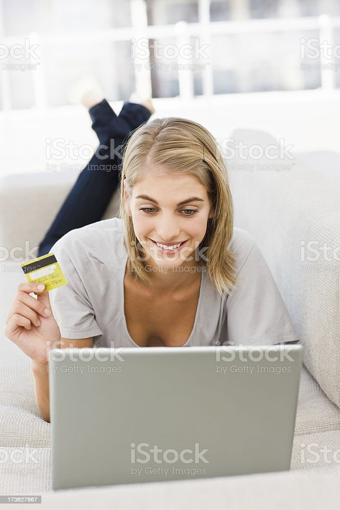 Young woman holding credit card and using laptop royalty-free stock photo