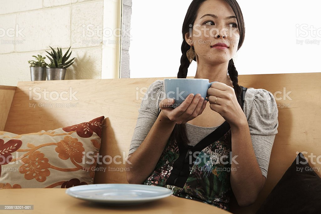 Young woman holding cup of coffee in cafe, looking away stock photo
