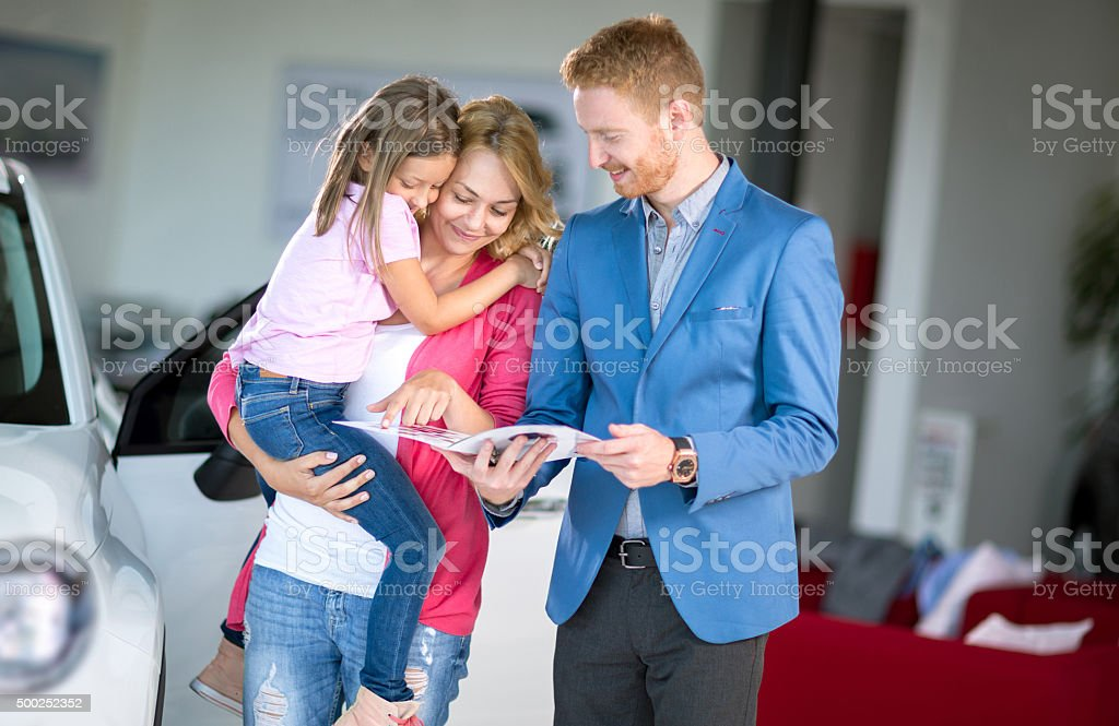 Young woman holding daughter talking with car dealer stock photo