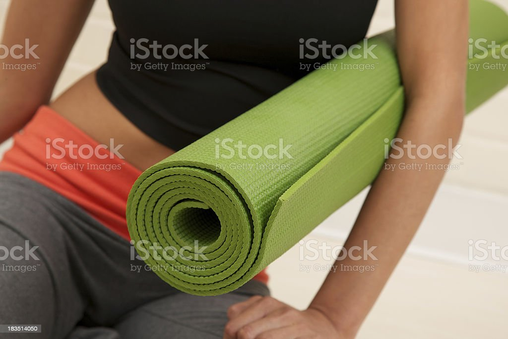 Young woman holding exercise mat royalty-free stock photo