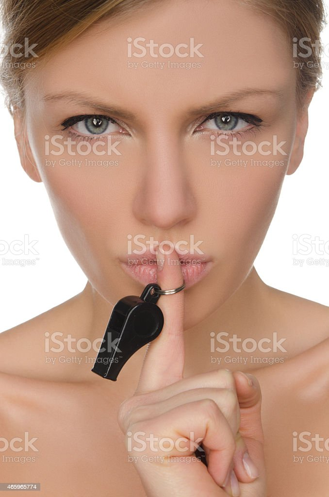 young woman holding finger and whistle before lips stock photo