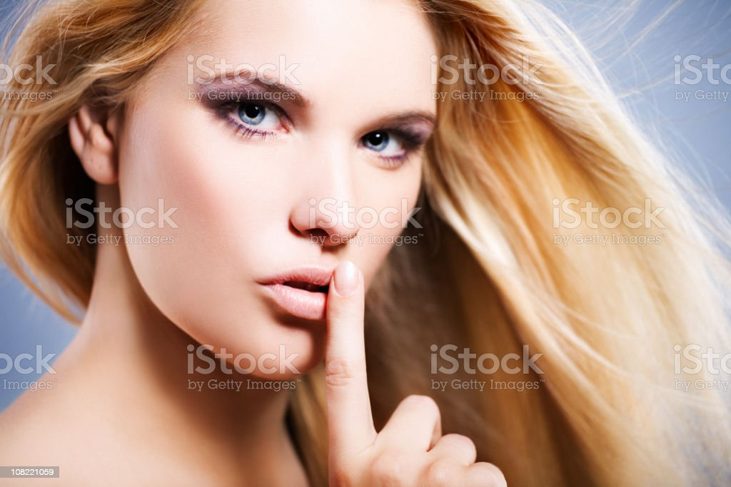 Young Woman Holding Finger to Lips royalty-free stock photo