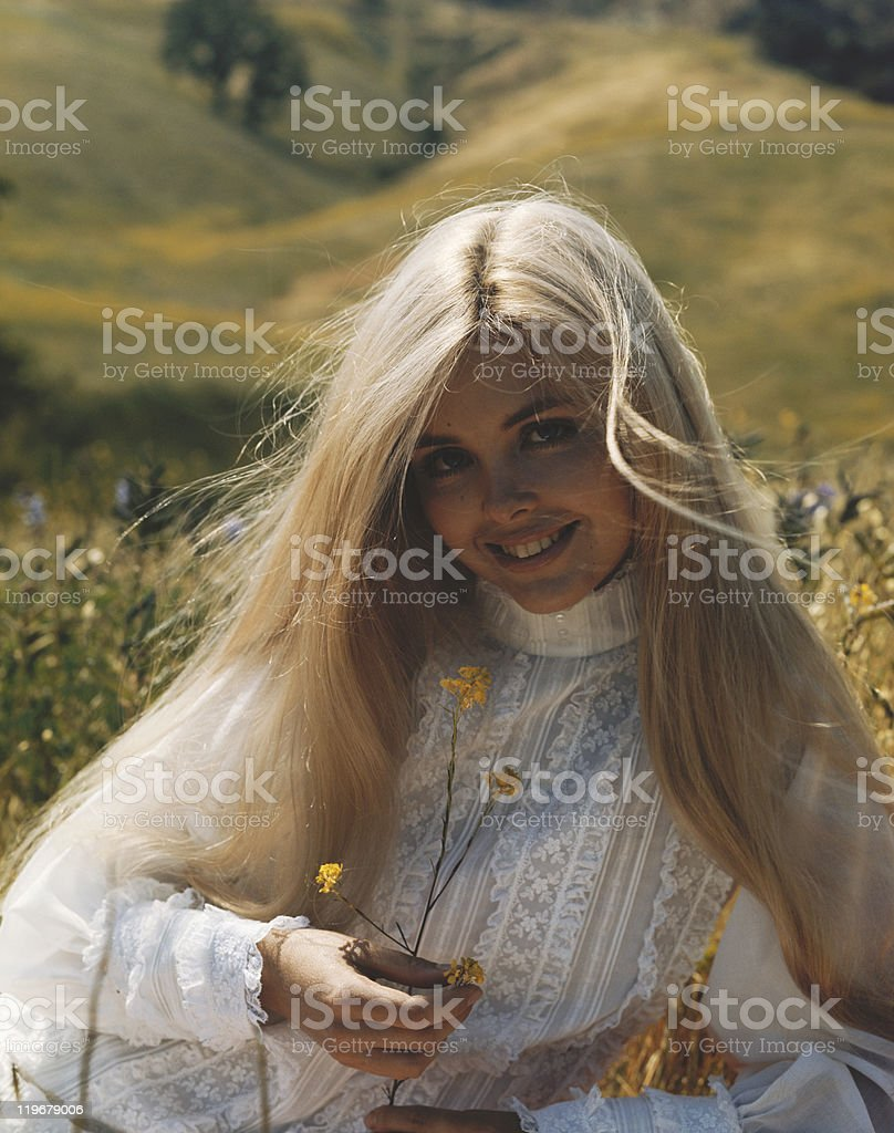 Young woman holding flower, smiling, portrait royalty-free stock photo