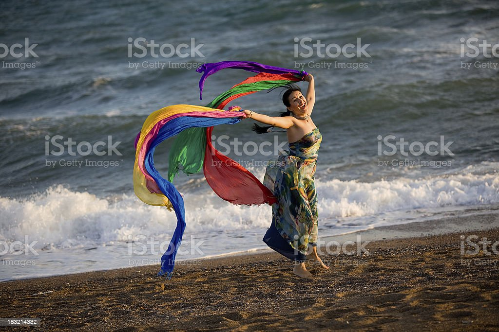 Young woman holding flying multicolored scarf in the beach royalty-free stock photo