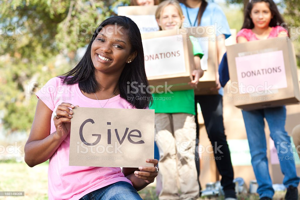Young woman holding Give sign in front of volunteers royalty-free stock photo