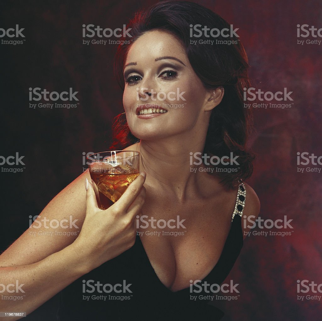 Young woman holding glass of beer, smiling, portrait, close-up stock photo