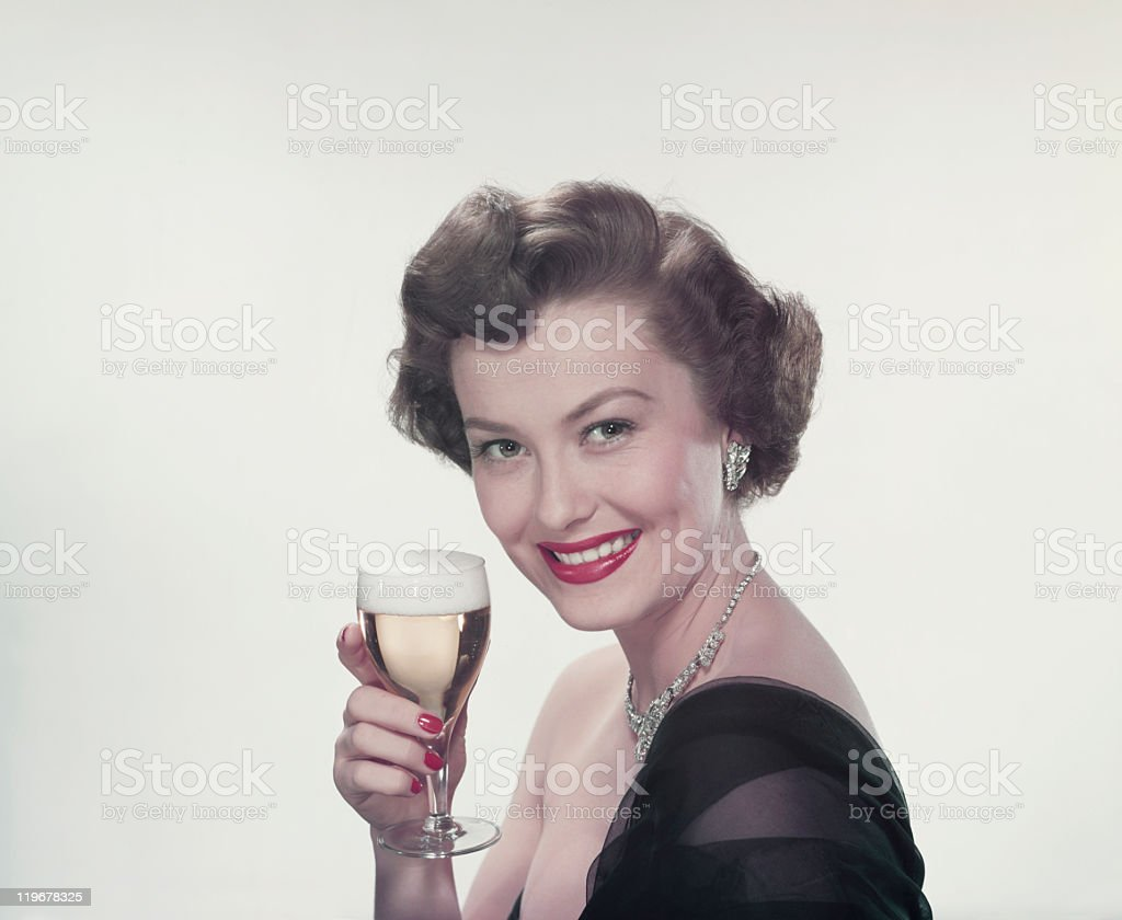 Young woman holding glass of wine, smiling, portrait stock photo