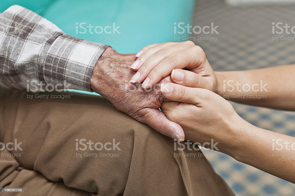 Young woman holding hand of elderly man royalty-free stock photo