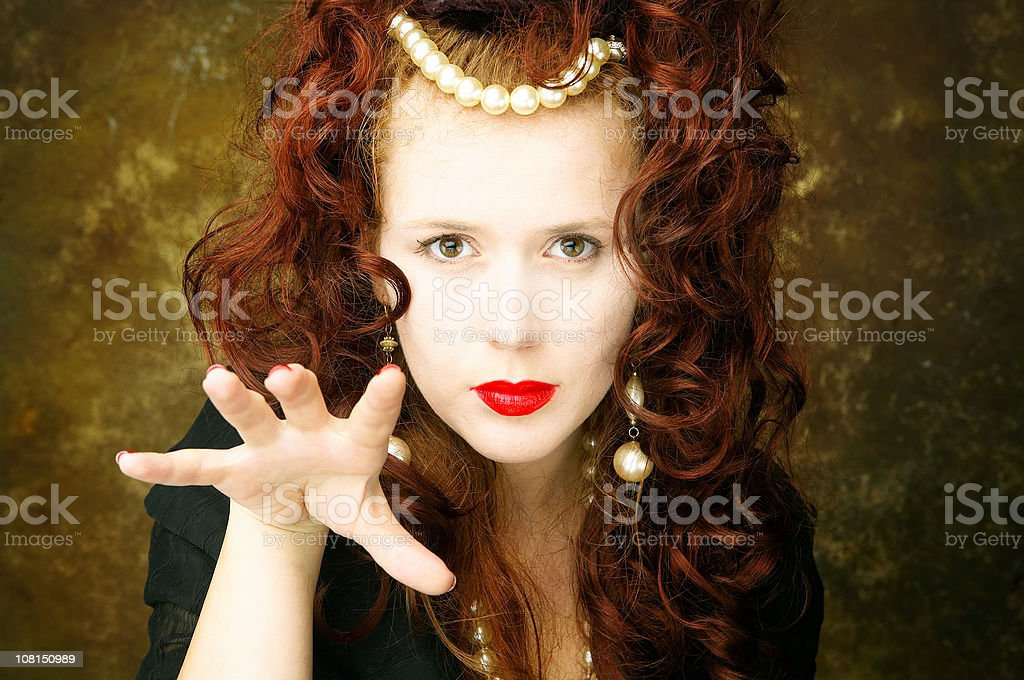 Young Woman Holding Hand Up and Wearing Pearls royalty-free stock photo