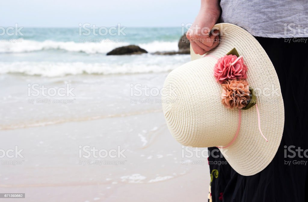 Young woman holding hat on the beach stock photo