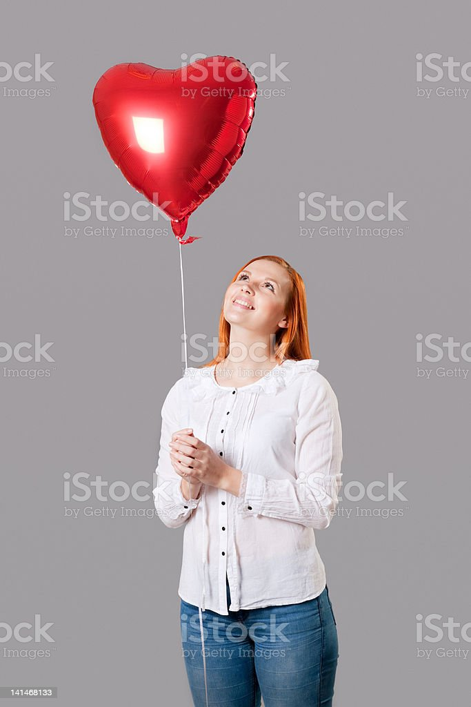 Young woman holding heart shaped balloon stock photo