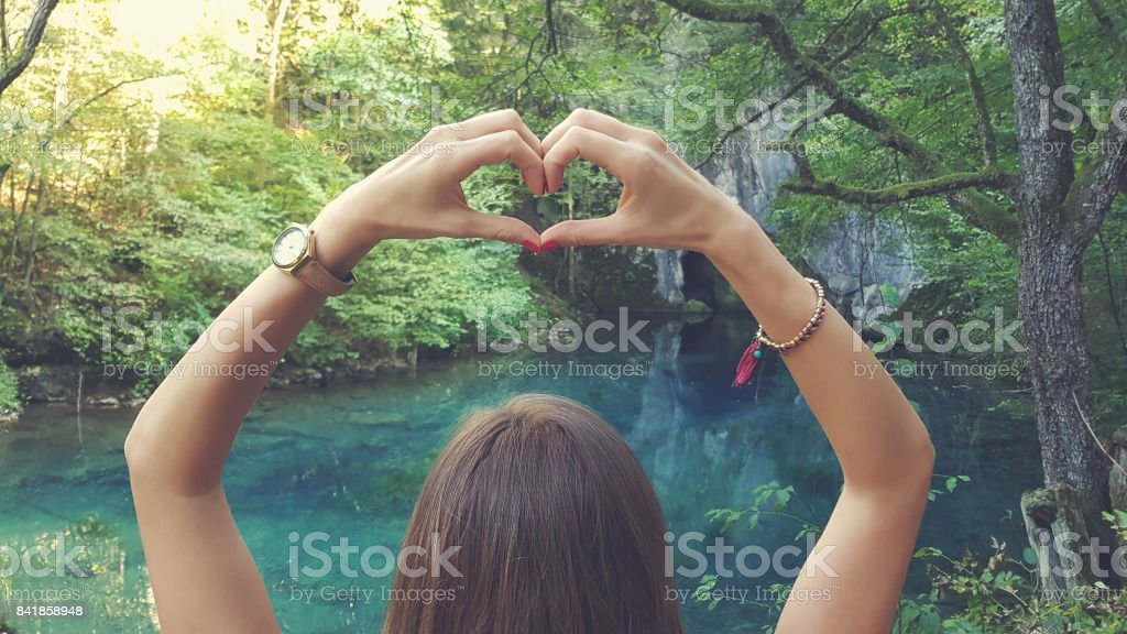 Young woman holding heart-shape for the beautiful nature. stock photo