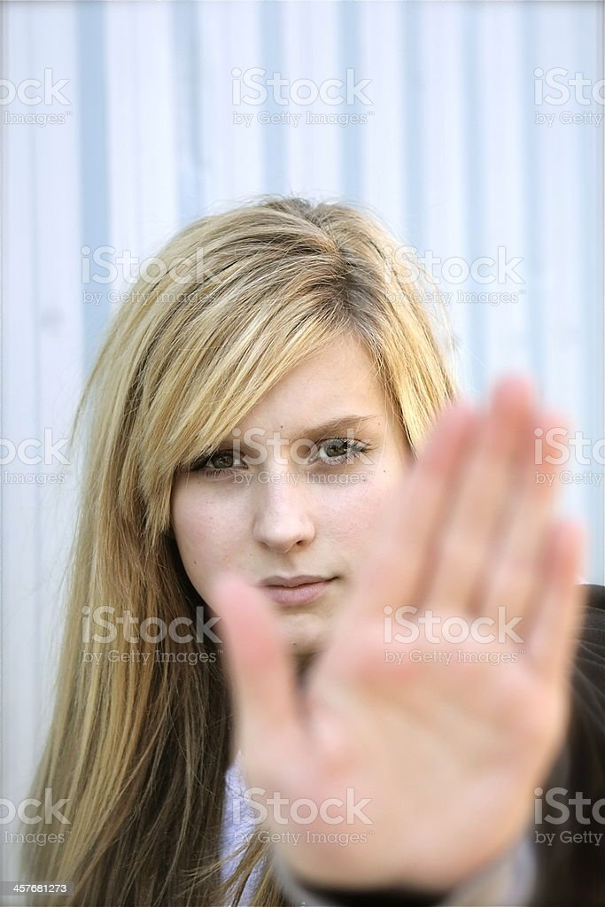 A young woman holding her hand out to say no stock photo