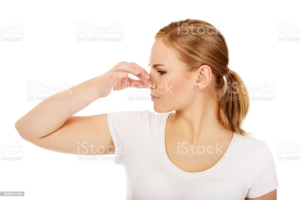 Young woman holding her nose because of a bad smell stock photo