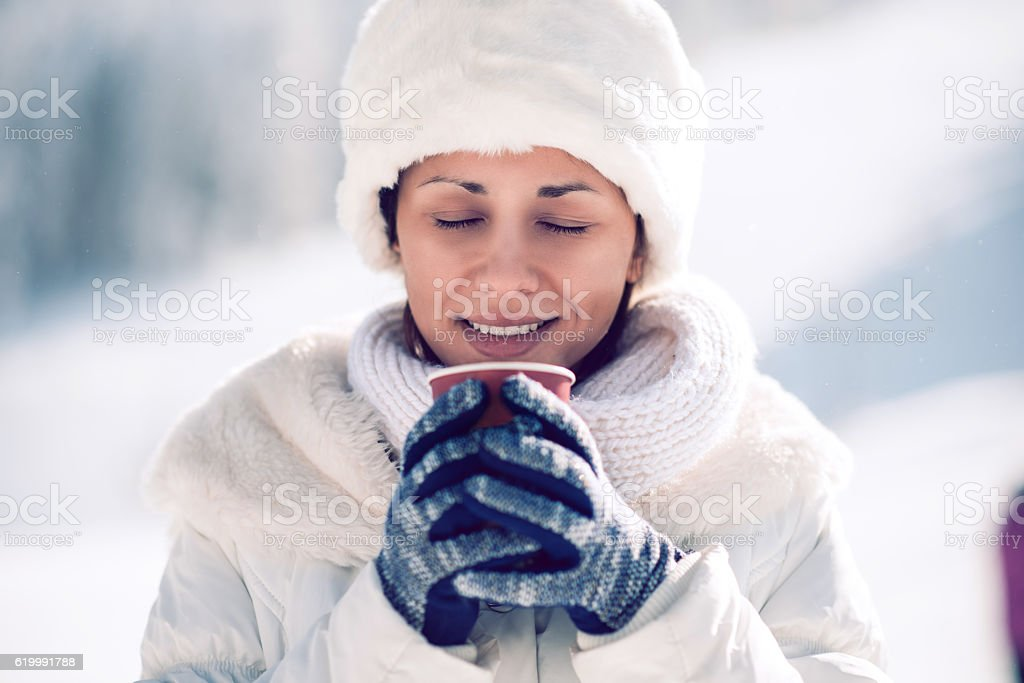 Young Woman Holding Hot Drink Mug Outdoor on Winter Snow stock photo