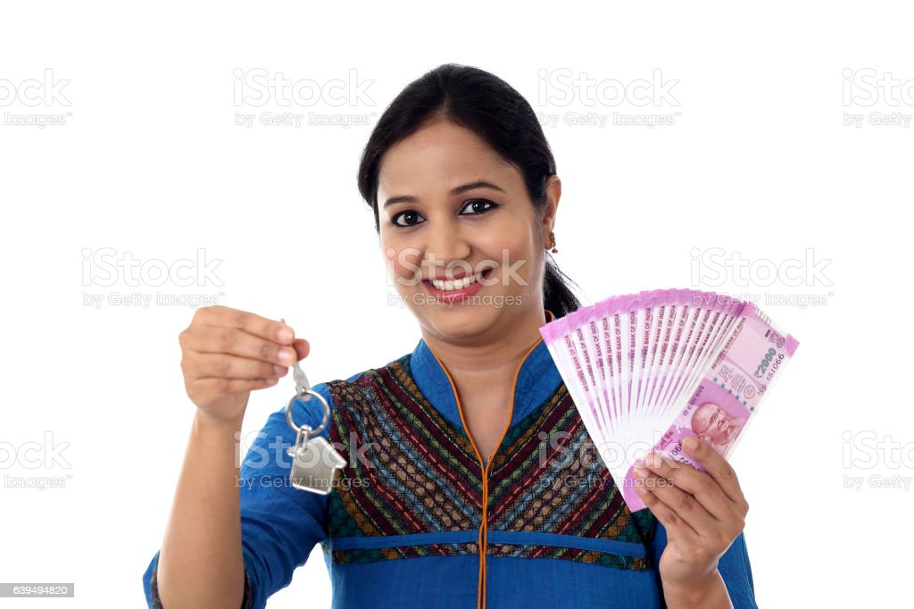 Young woman holding house shape key and 2000 rupee notes stock photo