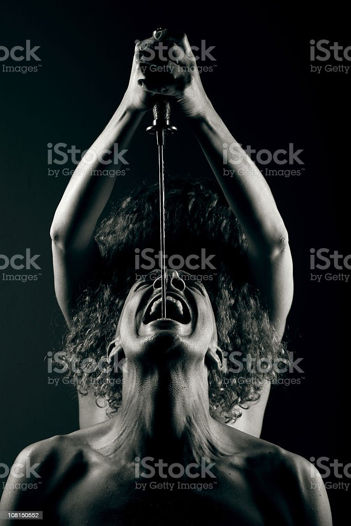 Young Woman Holding Knife Blade Over Man, Black and White stock photo
