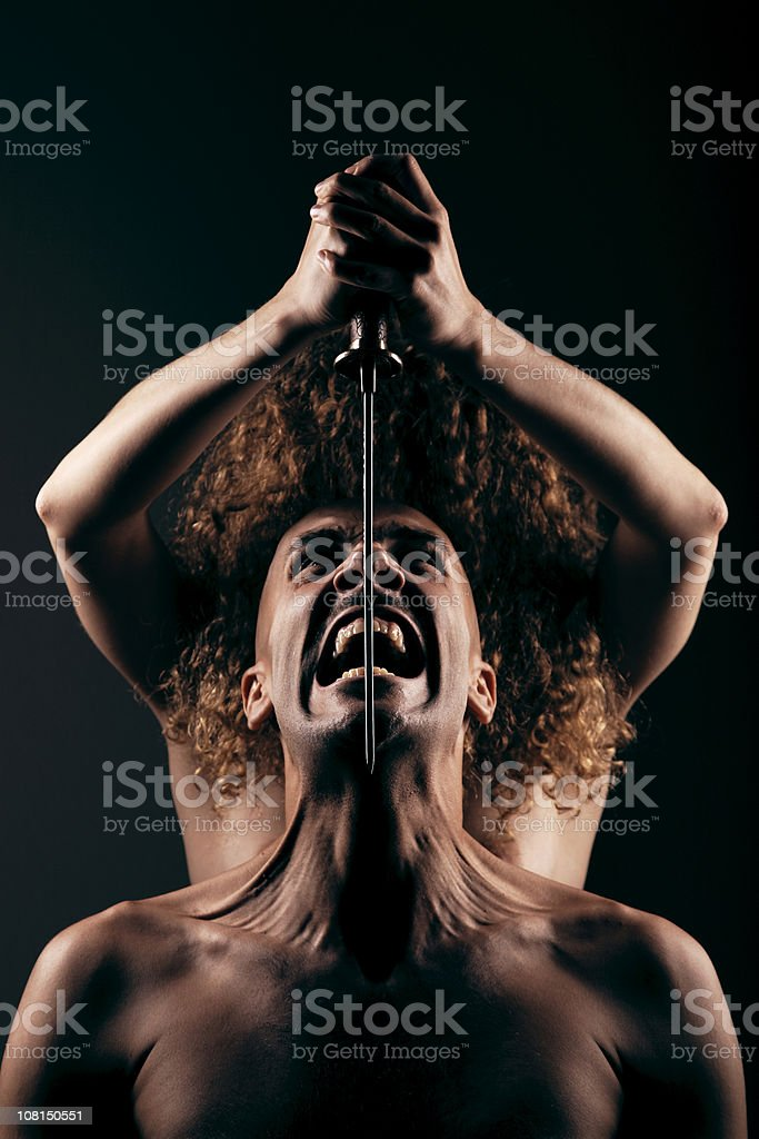 Young Woman Holding Knife Blade Over Man stock photo