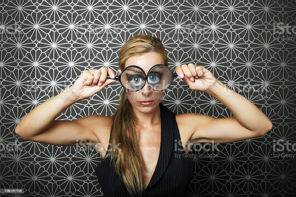 Young Woman Holding Magnifying Glasses To Both Eyes royalty-free stock photo