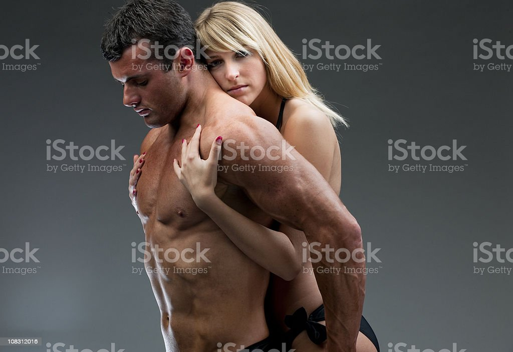 young woman holding nude muscular man XXXL royalty-free stock photo