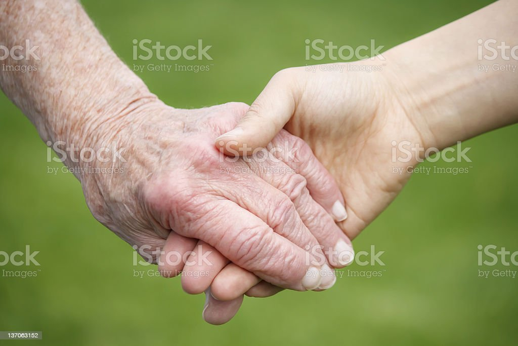 Young woman holding old woman's hand royalty-free stock photo