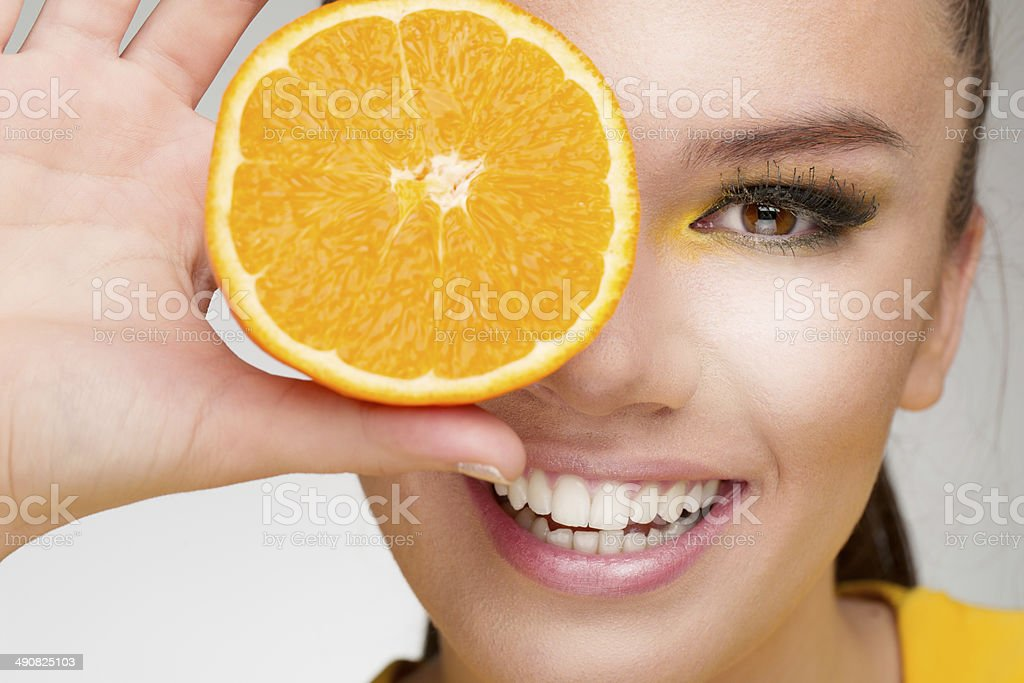 Young woman holding orange slice stock photo