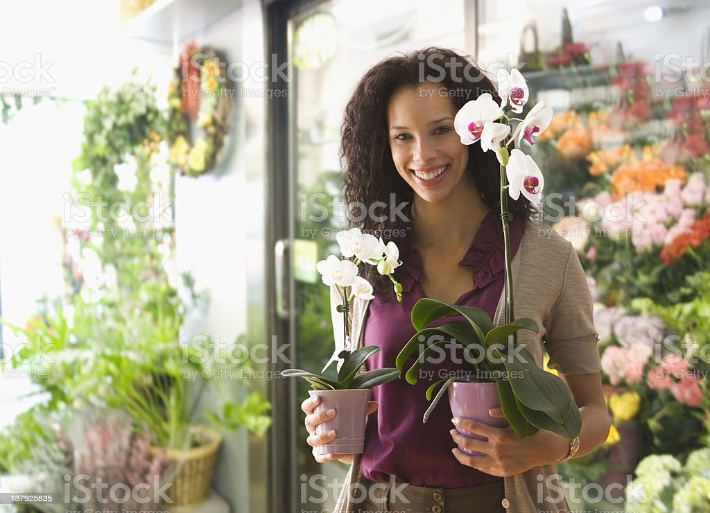Young woman holding orchids in a flower shop royalty-free stock photo