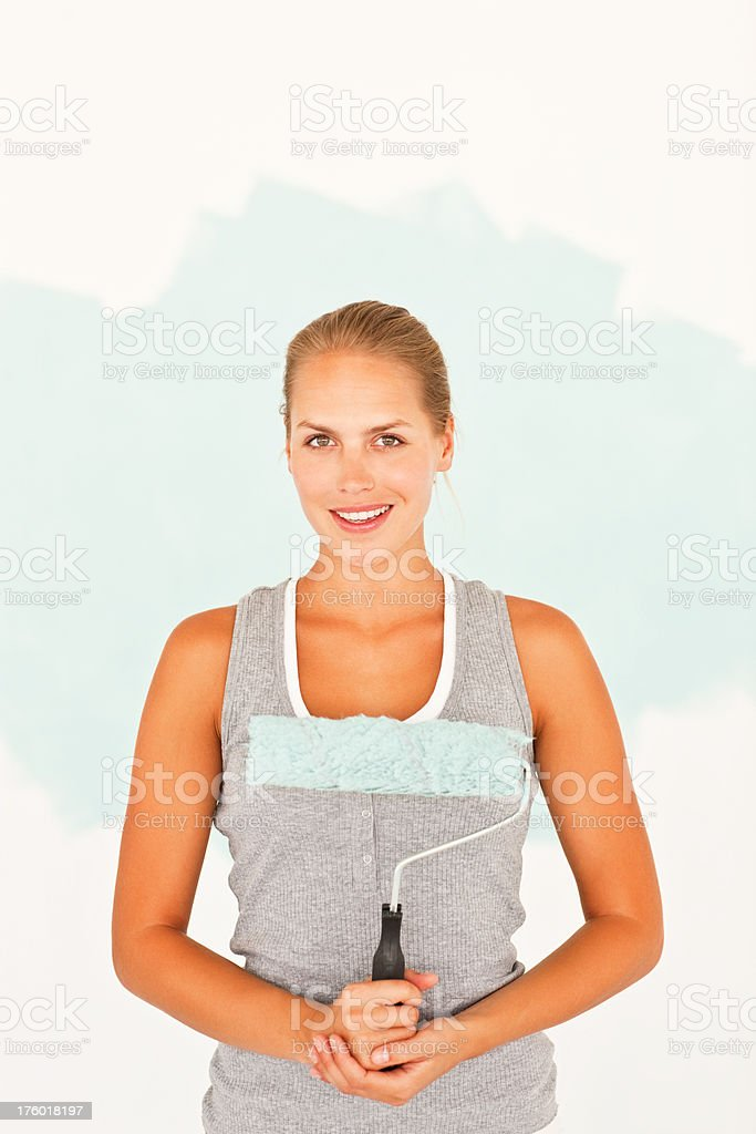 Young woman holding paint roller royalty-free stock photo